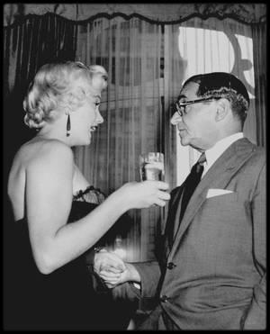 """9 Septembre 1954 / Photos George BARRIS, Marilyn reçoit des journalistes pour une conférence de presse donnée au """"Saint Regis Hotel"""" où elle loge durant son séjour à New York, pour les besoins du tournage de scènes en extérieures du film """"The Seven year Itch"""" (""""Sept ans de réflexion""""). Sous des airs de cocktail, cette conférence de presse, organisée par Leonard LYONS, rédacteur en chef du 'New York Post', est d'ailleurs donnée en l'honneur de Marilyn afin de marquer le début du tournage dans la ville de New York."""