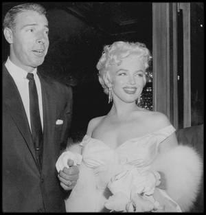 """1er Juin 1955 /  Marilyn, accompagnée de Joe DiMAGGIO, apparut à la première de « The seven year itch » au """"Loew's State Theater"""" de """"Times Square"""", à New York. Le théâtre, pour marquer l'événement, reçut une affiche de près de seize mètres de haut, représentant Marilyn, la jupe  retroussée. De nombreuses personnalités assistèrent à la projection, dont Grace KELLY, Henry FONDA, Tyrone POWER, Margaret TRUMAN, Eddie FISHER, Judy HOLLIDAY et Richard RODGERS, et des milliers de fans se rassemblèrent sur Broadway, dans l'espoir de l'apercevoir. Marilyn fêta en même temps ses vingt-neuf ans, à la réception donnée au """"Toots Shor's"""" (restaurateur et ami de DiMAGGIO), après la présentation du film. Tout le monde l'avait adoré dans le film, mais elle ne pouvait se réjouir de sa réussite, car STRASBERG l'avait conduite à critiquer violemment tout ce qu'elle avait accompli à Hollywood. Tous s'attendaient à ce qu'elle soit fière d'elle ce soir-là, mais la première avait produit sur elle l'effet opposé. Elle se disputa avec Joe, qui ne comprenait rien à ce qui se passait, et elle quitta la fête. Sam SHAW la raccompagna. A cette époque, et alors que peu de gens étaient au courant, Marilyn passait de plus en plus de temps avec Arthur MILLER ; ensemble ils faisaient de longues promenades dans """"Lower Manhattan"""", dînaient chez les ROSTEN ou, de façon plus intime, au """"Waldorf""""."""