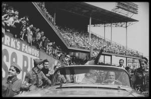 """12 Mai 1957 /  Marilyn arrive saluant la foule, en voiture décapotable au stade pour donner le coup d'envoi d'un match de football opposant les Etats-Unis à Israël à """"Ebbets Field"""" à Brooklyn (New York). Elle tapa si fort dans la balle qu'elle se foula deux orteils. Cette blessure ne l'empêcha pas de rester jusqu'à la fin du match et de remettre le trophée à l'équipe gagnante. (photos Bob HENRIQUES, Sam SHAW)."""