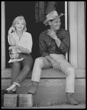"""1960 /  Photos Dennis STOCK, Marilyn et Clark GABLE lors du tournage du film """"The misfits"""", dans le Nevada / SYNOPSIS / L'histoire, située dans les environs de Reno, au Nevada, est celle d'une jeune femme paumée qui vient de divorcer, et qui va suivre au hasard d'une rencontre deux hommes aussi abîmés qu'elle, un ex-pilote de l'armée de l'air qui a perdu sa femme et un vieux cow-boy solitaire qui a raté sa vie. En route, ils rencontrent un quatrième larron, jeune orphelin à moitié fou, et s'en vont chasser ensemble les quelques derniers mustangs sauvages dans le désert racorni du Grand Ouest."""