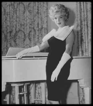 Avril 1958 / Marilyn pose devant son piano blanc (héritage de sa mère) tout en présentant la nouvelle robe sac dans son appartement de New York au 444 East 57th Street. L'appartement comptait trois chambres, deux salles de bains et un bureau. En 1957 Marilyn y habita avec Arthur MILLER, au treizième  étage, avec vue sur l'East River. En général les agents immobiliers de New York s'arrangeaient pour que le chiffre treize n'apparaisse pas et les immeubles passaient du douzième au quatorzième étage. Avec le décorateur John MOORE elle fit repeindre les murs en blanc et installer des miroirs du sol au plafond dans le salon-salle à manger, après avoir réuni les deux pièces. Le canapé, les fauteuils et les meubles étaient blancs, comme le piano qui l'accompagnait dans la plupart de ses déménagements. Dans son bureau, MILLER accrocha une photo de Marilyn prise par Jack CARDIFF en Angleterre sur le tournage de « The Prince and the showgirl » (1957). Bien qu'il eut déclaré que c'était sa photo préférée de Marilyn, il l'abandonna en partant : On dit qu'elle ne trouva jamais l'endroit achevé, bien qu'elle le gardât après le départ de MILLER, en 1960, et qu'elle y fît de nombreux travaux de décoration. Lena PEPITONE fut sa femme de chambre dans cet appartement. Cet appartement restera administrativement sa résidence principale jusqu'à son décès.