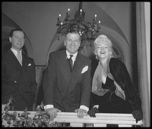 """9 Février 1956 / Le 9 février 1956, on organisa une conférence de presse à la """"Terrace room"""" du """"Plaza Hotel"""" pour annoncer au monde entier ce grand mariage cinématographique - celui du meilleur acteur classique d'Angleterre et de la plus grande séductrice d'Hollywood ; Bien qu'elle ait nié toute préméditation, il est évident que Marilyn orchestra l'événement à la perfection, volant la vedette au plus grand acteur vivant au monde, lorsqu'elle se pencha en avant et que l'une de ses fines bretelles se cassa net - un truc que les agents de publicité lui avaient, semble-t-il, appris à ses débuts à la Fox. Les photographes devinrent fous. On lui procura en toute hâte une épingle de nourrice, mais la bretelle céda encore deux fois avant que les journalistes et les photographes, ravis de l'incident, ne quittent la terrasse du """"Plaza Hotel"""" : Ce plan à l'organisation minutieuse valut la une à Marilyn, même si la conférence de presse en elle-même fut peu conviviale, les journalistes ayant tourné en ridicule sa """"prétention""""."""