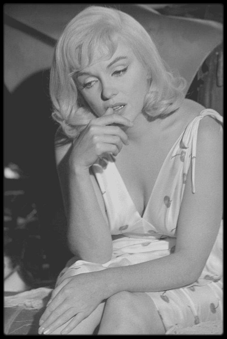 """1960 / Un tournage éprouvant, """"The misfits"""" : photos Elliott ERWITT, Eve ARNOLD et Bruce DAVIDSON / Autour du film ; John HUSTON ne s'attendait pas vraiment aux problèmes qu'il allait rencontrer avec Marilyn. « J'ai tout de suite vu qu'elle n'allait pas bien quand nous avons commencé à tourner, dira-t-il. Elle arrivait très en retard, et, apparemment, prenait des somnifères depuis pas mal de temps... Elle avait un regard bizarre et, les jours passant, semblait aller de plus en plus mal. » HUSTON n'avait revu Marilyn qu'une seule fois, et brièvement, depuis le tournage de """"Quand la ville dort"""" (Asphalt jungle), et ils avaient l'un comme l'autre beaucoup changé. Le cynisme de HUSTON s'était épanoui en un sadisme raffiné, et Marilyn était devenue une actrice accomplie, à qui les avatars de sa vie privée faisaient toucher le fond de la tristesse. Elle n'était plus la même dans """"Les Désaxés"""" (The misfits). La perruque lui enlevait un peu de son aura, et les yeux lourdement cernés par le maquillage qui masquait en partie le « regard bizarre » étaient peut-être ceux de la jeune divorcée de Reno, mais l'ensemble ne ressemblait plus tout à fait à Marilyn — celle de """"Sept ans de réflexion"""", """"Bus Stop"""", et """"Certains l'aiment chaud"""". / La fatigue, la souffrance et les déceptions avaient laissé leur marque. Elle avait perdu un peu de son éclat, même si les photographes et les journalistes qui se succédaient sur le plateau de façon ininterrompue ne s'en apercevaient pas encore. Alice McIINTYRE, du magazine """"Esquire"""", trouva Marilyn « d'une stupéfiante beauté ». Le photographe Henri CARTIER BRESSON vit dans sa beauté radieuse « une illustration mythique de ce que nous appelons en France la femme éternelle ». Une photographe, toutefois, ne trouva peut-être pas si éternelle cette femme : Inge MORATH, la photographe de """"Magnum"""", qui était arrivée avec CARTIER BRESSON et resta sur place pour devenir la prochaine Mrs. MILLER. / Marilyn allait devoir se plier à un plan de tournage charg"""