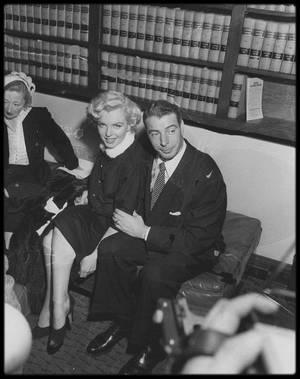 """14 Janvier 1954 / Marilyn épousa Joe DiMAGGIO à l'hôtel de ville de San Francisco. Ils souhaitaient un mariage aussi discret que possible, et Marilyn ne prévint le studio, par le biais d'Harry BRAND, chef de publicité de la Fox, qu'une heure avant la cérémonie. Malgré cela, plus de cent journalistes et reporters envahirent l'entrée et le couloir de l'hôtel de ville. Joe voulait l'épouser religieusement, mais l'archevêque de San Francisco, John MITTY, refusa de reconnaître la validité de son  divorce d'avec son ex-épouse, Dorothy ARNOLDS.  Il n'y eut donc qu'un mariage civil, célébré par l'officier municipal, le juge Charles S. PERRY. La cérémonie débuta à 13 h 48 et se termina trois minutes plus tard. Marilyn n'eut pas d'invité personnel ; seuls la famille et les amis de Joe (Jean et Lefty O'DOUL, Tom DiMAGGIO et sa femme Lee, et George SOLOTAIRE) assistèrent à la cérémonie. Le témoin de Joe fut Reno BARSOCCHINI. Sur le registre, Joe inscrivit son âge (trente-neuf ans) et signa ; Marilyn donna son nom légal, Norma Jeane MORTENSEN DOUGHERTY, mais se rajeunit de trois ans et nota qu'elle avait vingt-cinq ans. Elle portait un tailleur en drap brun fonce avec un col en hermine et tenait dans sa main trois orchidées. A leur sortie de l'hôtel de ville, ils furent assaillis par une foule de deux cents photographes et journalistes, et trois cents fans ; ils sautèrent dans le Cadillac bleu nuit de Joe (immatriculée Joe D) et passèrent leur premier jour de lune de miel au  """"Clifton Motel"""", à Paso Robles (Californie). Le lendemain Marilyn appela son avocat, Lloyd WRIGHT pour avoir des nouvelles et ses messages ; en guise de compliment pour ce mariage, la Fox l'avait réintégrée dans son statut d'actrice maison. Darryl ZANUCK n'eut pas d'autre choix que de lever sa suspension. Dans le cas contraire, la presse et le public ne le lui auraient pas pardonné. On allait à nouveau la payer et on la priait respectueusement de revenir le 20 janvier (au plus tard le 25 janvier) sur la pla"""