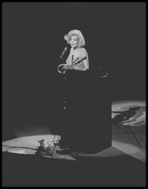 """19 Mai 1962 / Marilyn est conviée au gala d'anniversaire de John F KENNEDY ; Elle est vêtue d'une somptueuse robe de soie (créée par le couturier Français Jean Louis) cousue à même son corps, sous laquelle elle ne porte aucun sous-vêtement, et porte une fourrure d'hermine blanche qu'elle aurait empruntée au département costumes de la Fox (qui ne cautionne pas la venue de l'actrice au Gala de JFK). Une foule de 15 000 démocrates sont venus acclamer les 45 ans de leur président au """"Madison Square Garden"""" à New York. Jackie KENNEDY, la femme du président, est absente. Ayant consulté la liste des invités, elle a emmené ses enfants faire du cheval en Virginie. Jack BENNY, Henry FONDA, Ella FITZGERALD, Peggy LEE, Diahann CARROLL et Maria CALLAS doivent se produire. Après avoir abusé du """"Dom Pérignon"""" (marque prestigieuse de champagne) dans sa loge car pétrifiée par le trac, c'est comme à son habitude que Marilyn arrive avec environ 40 minutes de retard. C'est après plusieurs annonces infructueuses pendant lesquelles les roulements de tambours et les projecteurs éclairent une scène vide, que Peter LAWFORD (le beau frère de JFK) présente Marilyn en des termes plutôt ambigus: """"Mr. President, the Late Marilyn MONROE"""" [""""late"""" voulant aussi bien dire """"en retard"""" que """"décédée""""]. Marilyn chante sur scène le désormais mémorable """"Happy Birthday"""" et """"Thank you for the memory"""". Puis le Président exprime sa reconnaissance à la chanteuse en déclarant: """"Maintenant que j'ai entendu un """"Happy Birthday"""" chanté d'une façon aussi douce et agréable, je peux me retirer de la politique"""". / PAROLES DE LA CHANSON /"""