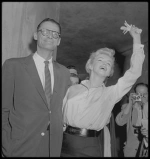 """22 Juin 1956 /  MILLER fut de retour à New York. Il consulta son avocat Lloyd GARRISON, à son cabinet, """"Le PAUL, WEISS, RIFKIND, WHARTON et GARRISON"""", sur Madison Avenue. Il n'était pas question pour le Département d'Etat d'accorder un passeport à MILLER sans une déclaration sous serment écrite qui affirmait qu'il n'avait jamais été membre du Parti Communiste. Joseph RAUH, l'avocat de MILLER à Washington, avait préparé un brouillon pendant le week-end et l'avait envoyé à Lloyd GARRISON pour que MILLER le revoie et le signe. Il demanda à MILLER de signer une autre déclaration comportant des passages de son oeuvre littéraire et d'interviews qui indiquaient bien sa foi en la démocratie. Si la Commission recommandait une accusation pour outrage, le Département d'Etat n'accorderait sûrement pas son passeport à MILLER. Marilyn avait rendez-vous chez sa psychanalyste. Le Dr HOHENBERG qui exerçait toujours une énorme influence sur la vie privée et publique de Marilyn, approuva ce mariage. Elle conseilla alors à Marilyn d'affronter la presse immédiatement. A 16 heures 30 ce jour là, Marilyn convoqua une conférence de presse en bas de son immeuble. Elle apparut main dans la main avec Arthur, devant le hall de Sutton Place."""