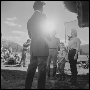 """25 Juillet 1953 / Marilyn arrive à Jasper (Canada) pour les extérieurs du film """"River of no return"""" ; L'hostilité régna sur le plateau lorsque le réalisateur Otto PREMINGER et Marilyn entamèrent une guerre d'usure. PREMINGER fit clairement comprendre qu'il travaillait sur ce film uniquement parce qu'il en était redevable par contrat à la Fox ; Darryl ZANUCK lui fit miroiter la technologie du nouveau Cinémascope, et certains critiques notèrent que PREMINGER avait plus envie de filmer le paysage spectaculaire que d'arracher une interprétation dramatique à ses acteurs. Comme  bon nombre de ses confrères il avait interdit au professeur d'art dramatique de Marilyn, Natasha LYTESS, l'accès au tournage, pour ne la rappeler que si le siège de la Fox le lui demandait comme une faveur. Physiquement, ce fut un rôle très exigeant pour Marilyn, une grande part de l'action impliquant de faire tomber les protagonistes dans la rivière lors du franchissement de ses effrayants rapides. Pour ses scènes, il fallut tremper Marilyn avec des seaux d'eau pour les raccords. PREMINGER insista pour que ses vedettes fassent elles-mêmes leurs cascades, ce qui ne fut pas sans conséquences. Ainsi le radeau de Marilyn et de son partenaire Robert MITCHUM resta bloqué dans les rapides, et il fallut les secourir. Dans ce film, Marilyn devait interpréter quatre chansons de Ken DARBY et Lionel NEWMAN, et elle répéta inlassablement « One silver dollar », « I'm gonna file my claim », « Down in the meadow » et la chanson-titre « River of no return », jusqu'à l'approcher de la perfection. L'été où le film sortit, RCA vendit plus de 75 000 disques de « I'm gonna file my claim » en trois semaines seulement. Les deux dernières semaines de tournage, Joe DiMAGGIO rejoignit Marilyn, notamment parce qu'elle avait été victime d'un accident : durant le tournage, elle était tombée du radeau dans l'Athabasca. Un médecin local diagnostiqua une possible entorse; les médecins du studio ne virent là rien de sérieux, mais"""
