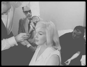"""1960 / TESTS COIFFURES pour le film """"The misfits"""" / LES CHEVEUX DE MARILYN, L'HISTOIRE D'UN PUR CALVAIRE / La saga capillaire de Marilyn débute alors qu'elle n'était qu'une jeune mannequin : en 1946, travaillant pour l'agence """"Blue Book Modeling"""", elle participe à un casting pour une publicité de shampooing """"Rayve"""". La photographe la trouve à son goût mais souhaite qu'elle se raidisse les cheveux « qui prennent mieux la lumière en pellicule couleur« . Sur sa fiche signalétique de l'agence, est inscrit « Medium blonde : too much curled and unruly, discoloring and perm recommended. » (« Blond moyen : trop de boucles indisciplinées, décoloration et permanente recommandées« ). La coiffeuse Sylvia BARNHART qualifiera, elle, sa chevelure de « frisée marron terne », au Salon """"Franck & Joseph"""" vers lequel on l'adresse, sur Wilshire Boulevard. Un établissement à la mode et côté à l'époque, fréquenté par de nombreuses stars, de Rita HAYWORTH à Ingrid BERGMAN. Un premier défrisage Ce processus de défrisage entraîne une première décoloration tendant vers le roux, ce que la jeune-femme apprécie. Elle demande alors à l'accentuer pour l'éclaircir davantage, « fair« . Enfant, Marilyn précisera qu'elle était blond platine et qu'on la surnommait alors « tête d'étoupe », elle rêvait alors de cheveux blonds dorés. Jusqu'à ce qu'elle découvre le blond platine de la magnifique Jean HARLOW. Il lui faudra alors 3 ans de tests et d'ajustements pour « fabriquer » la Marilyn emblématique que l'on connaît. Du blond vénitien aux blond doré, blond cendré jusqu'au blond champagne… Mais quelle était la nature des cheveux de l'héroïne des Hommes préfèrent les blondes ? Sa coiffeuse Gladys RASMUSSEN dévoilera à leur sujet : « Les cheveux de Marilyn posent plusieurs problèmes : ils sont très fins et difficiles à travailler. Trop gras pour ne pas être lavés tous les jours et spontanément si frisés que je dois les lisser très soigneusement à la moindre occasion. Quant à la recette de son blond platine,"""