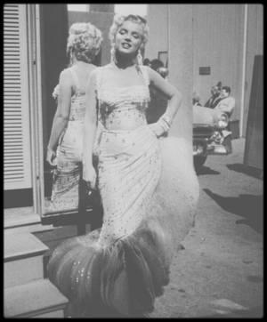"""1954 / Marilyn (et les autres acteurs du film tels Dan DAILEY, Donald O'CONNOR, Mitzi GAYNOR, Ethel MERMAN ou encore Johnnie RAY) lors des répétitions de la scène finale du film """"There's no business like show business"""" (La joyeuse parade) ; Le rôle secondaire tenu par Marilyn dans cet hommage au compositeur Irving BERLIN était un compromis, à la convergence de divers intérêts. D'abord, il compensait son refus d'apparaître dans « Pink tights », un film qu'elle avait repoussé malgré l'insistance du studio. Ensuite, il la ramenait à Los Angeles, après qu'elle eut vécu deux ou trois mois à San Francisco avec son nouveau mari, Joe DiMAGGIO. Enfin, il offrait à Marilyn  le genre de concessions qu'elle rêvait d'obtenir : on lui permit d'être encadrée par sa propre équipe - ses professeurs d'art dramatique Natasha LYTESS, de chant Hal SCHAEFER, et de danse Jack COLE, qu'elle préférait apparemment à Robert ALTON, le chorégraphe engagé par le producteur Sol C. SIEGEL. En outre, selon la plupart des biographes, on lui avait promit un projet qui lui plaisait bien d'avantage, « The seven year itch » (1955). Le premier scénariste, Lamar LOTTI, mourut d'une crise cardiaque avant d'avoir pu achever le script. Le tandem formé par Henry EPHRON et sa femme Phoebe prit la relève, mais du propre aveu d'Henry : « Je pense que ce fut notre travail le plus pénible. De par la nature de l'histoire, toutes les scènes étaient des clichés ». Le personnage de Marilyn, Vicky, brossé à la hâte et greffé sur l'intrigue originale, hérita de certaines chansons que devait interpréter à l'origine Ethel MERMAN. Le mélange de talents qui en résultait était bizarre à tous points de vue : la plupart des critiques jugèrent que l'association de Marilyn, de son amoureux au visage poupin, Donald O'CONNOR, et de l'effrontée Ethel MERMAN manquait vraiment de crédibilité. Les relations de Marilyn  avec le réalisateur, Walter LANG, furent particulièrement mauvaises. On raconte que LANG ne manqua pas une occasion d"""