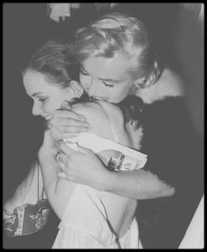"""5 Octobre 1955 / Marilyn se rend à la Première de la pièce de théâtre """"The diary of Anne FRANK"""", au """"Cort Theater"""" de New-York, avec dans le rôle principal Susan STRASBERG, fille de Lee et jeune amie de Marilyn, qui d'ailleurs vient la féliciter dans sa loge après sa performance ; la soirée se poursuit au """"Sardi's restaurant"""" pour un dîner. / Susan relatera dans ses mémoires, notamment dans le livre """"Marilyn et moi"""", qu'elle considérait la star comme sa soeur de substitution. Susan STRASBERG a quinze ans lorsque Marilyn débarque à New York... et chez elle. L'adolescente est à la fois fascinée et jalouse de cette grande s½ur tombée du ciel, qui monopolise l'attention de son père, directeur de """"l'Actor's Studio"""". Dès lors, les STRASBERG vivent au rythme des crises de larmes ou de fou rire de la star, la suivent sur la crête ou dans le creux de la vague. Marilyn joue, rit, aime, pleure. Susan savoure, heureuse de la complicité qui les unit, et fait ses débuts sur les planches. Elle rêve d'une chose : que son père soit fier d'elle. Mais celui-ci est bien trop occupé avec Marilyn... Pas facile de rivaliser avec un mythe hollywoodien, même devant ses parents ! Non, tout n'a pas été déjà dit sur Marilyn. Loin du strass et des paillettes, voilà une femme généreuse, drôle, envahissante... et tellement attachante."""