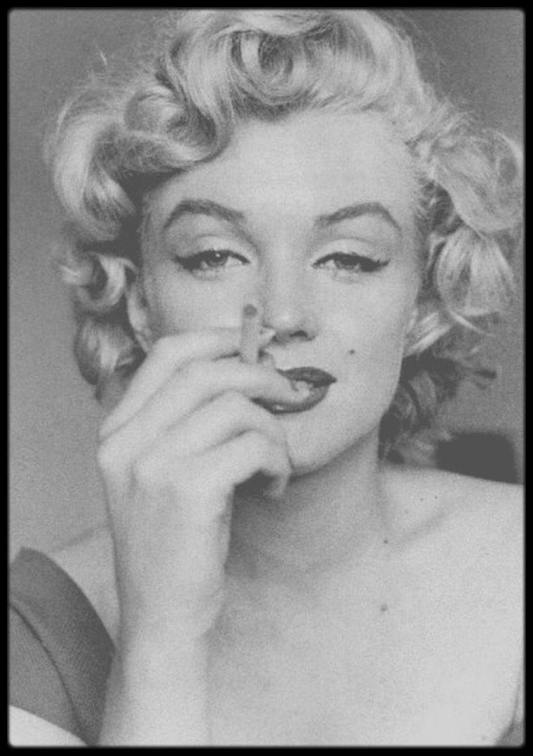 """1952 / (Photos Jock CARROLL) Marilyn lors du tournage du film """"Niagara"""" / Le rendez-vous était pris à dix heures du matin: Marilyn ne se sentait pas bien et rappela Jock à midi. Dans la chambre d'hôtel de Marilyn, Jock notifia quelques affaires: une pendule, quelques vêtements, beaucoup de livres et une photo de Joe. Ils discutèrent de sujets variés: de relaxation (la technique de Marilyn était de courir dans la chambre), de psychanalyse (FREUD), de son enfance (où elle lui raconta que des souvenirs heureux). Une fois qu'elle fut prête, elle lui suggéra de la prendre en photo en train de fumer une cigarette, tel qu'elle le faisait dans ses films: à la """"française"""", roulant la cigarette dans sa bouche."""