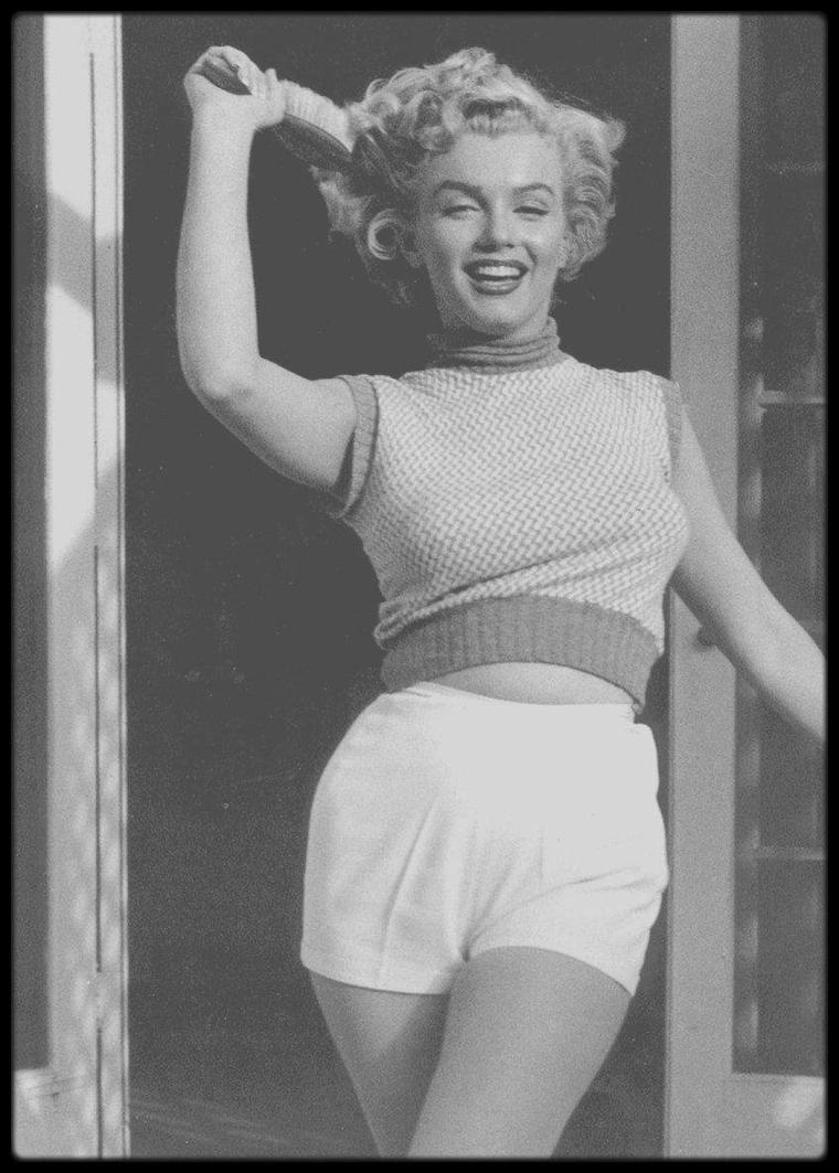 """1953 / Marilyn sur la terrasse du """"Bel air Hotel"""" sous l'objectif du photographe Andre DE DIENES / Il apprit seul la photographie. Il vécut et travailla à Rome, Paris et Londres. Il arriva aux Etats-Unis en 1938, avec l'aide d'Arnold GINGIRCH du magazine """"Esquire"""", et ouvrit un studio de photos à New York. David O.SELZNICK, producteur indépendant, le fit venir à Hollywood en 1944, pour photographier Ingrid BERGMAN. En 1945, il acquit une solide réputation de photographe. Il avait 32 ans, la carrure avantageuse et les yeux bleus lorsqu'il rencontra Norma Jeane, en novembre 1945, par l'intermédiaire de la """"Blue Book Modeling Agency"""". Il prit les premières photos de Norma Jeane en 1945. C'étaient les photos d'une jolie fille, typiques de l'époque : sur la route 101, au nord d'Hollywood, ou dans un champ avec un agneau nouveau-né, en blue-jean et chemisier rouge, ou sur la plage de Malibu en short et pull-over."""
