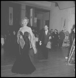 """26 Janvier 1952 / (Part II) Ce jour là se tient la cérémonie des """"Henrietta Awards"""" à Santa Monica, qui prit place au """"Del Mar Club"""". Marilyn reçoit des mains de lex BARKER et de sa femme Arlene DAHL, le prix """"Henrietta"""" de la """"Meilleure jeune personnalité du box office 1951"""". Au cours de cette soirée, Marilyn a été vue au côté de Charlie CHAPLIN Jr. (le fils de), avec qui elle eut une brève aventure. Parmi les autres invités figurent Tony CURTIS, Dean MARTIN, Bob HOPE, Alan LADD, Joan CRAWFORD, Jane WYMAN, Gregory PECK, Mitzi GAYNOR, Leslie CARON, Esther WILLIAMS, Errol FLYNN, John DEREK,  Janet LEIGH... Les """"Henrietta Awards"""" seront ensuite remplacés par les """"s'Foreign Press Awlard"""" puis par les """"Golden Globe Awards"""". Marilyn portait une robe au décolleté vertigineux, ce qui lui vaudra pas mal de critiques, dont une assez cinglante de la part de Joan CRAWFORD, qui dira """"qu'elle aurait bien plus d'allure que si elle portait un sac à patates"""" ; Marilyn relèvera le défit et se fera faire une robe justement en toile de jute, dans un sac de pommes de terre, qui lui ira à merveille. (voir photo ci-dessus)."""