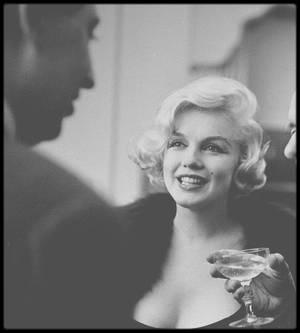 """26 Février 1959 / (PART II) (Photos Paul SLADE) UNE ETOILE DE CRISTAL POUR UNE ETOILE DE CINEMA / Heureux toutous ! Le 26 Février 1959, dans un salon du Consulat de France à New York, Marilyn joue avec les teckels de monsieur le Consul ; elle va recevoir dans quelques minutes l'étoile de cristal pour la meilleure actrice étrangère dans le film """"The Prince and the showgirl"""". Ancêtres des Césars, les étoiles de cristal  furent décernées par l'Académie du cinéma français, à l'instigation du compositeur Georges AURIC, de 1955 à 1975."""