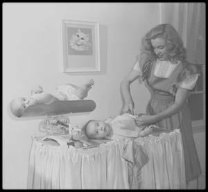 """13 Janvier 1947 / Harry BRAND, publicitaire à la Fox et son équipe, firent passer dans le """"Los Angeles Times"""", une photo de Marilyn avec cette  légende : « La baby-sitter débarque au cinéma ». L'article expliquait, la rajeunissant de deux ans, que cette « blonde baby-sitter de dix-huit ans avait rencontré un recruteur de talents » et s'était trouvée immédiatement propulsée vers la gloire. Ils concoctèrent à Marilyn une biographie édulcorée, faisant officiellement d'elle une orpheline, en passant sa mère sous silence. (Photos Dave CICERO)."""