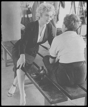 """1952 / (Photos Jock CARROLL) Marilyn en tailleur noir lors du tournage du film """"Niagara"""". / Un critique de l'époque l'affirmait : """"Ce film authentifie deux chefs-d'½uvre de la nature : le Niagara et Marilyn."""" Il reste pourtant l'un des films les moins connus de l'actrice – qui s'impose là définitivement comme sex-symbol –, bien qu'il soit l'un des plus représentatifs de la palette de son talent. Un film étrangement vénéneux, littéralement transcendé par sa mise en scène, que l'on doit au vétéran Henry HATHAWAY (""""Peter Ibbetson"""", """"Les Trois Lanciers du Bengale"""", """"Prince Vaillant""""). Atmosphère poisseuse à la James CAIN, éclat du technicolor qui magnifie la crudité du désir illustrée par la robe rouge de Marilyn et les tourments de la vie symbolisés par les chutes du Niagara, ce film met en scène deux couples que tout oppose, pour une intrigue digne des films noirs, où le désir et la mort mènent la danse. Première grande idée du cinéaste : assembler Marilyn MONROE et le sombre Joseph COTTEN (""""Citizen Kane"""", """"L'Ombre d'un doute"""") pour former un couple d'amants terribles, à la fois fous amoureux et complètement névrosés. Deuxième grande idée : leur opposer comme revers négatif un couple conformiste au possible, incarné par Jean PETERS et Casey ADAMS. Enfin, dans un technicolor flamboyant, les chutes du Niagara constituent un personnage à part entière, qui ouvrent et concluent ce film majestueux, vénéneux et tourmenté."""