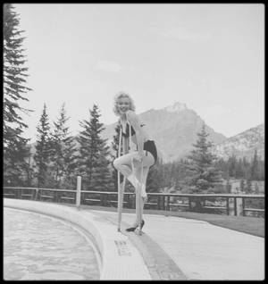 """1953 / « Hollywood débarque au Canada ! » (Pendant l'été 1953, on filme deux autres westerns dans les Rocheuses, et l'hôtel """"Banff Springs"""" sert de Q.G.) Plutôt habitué à tirer platement le portrait de l'Américain moyen, John VACHON ne sait pas trop par quel bout de la lorgnette honorer cette affectation. Dans des lettres envoyées à sa femme, il se moque du vedettariat et de l'entourage zélé de Marilyn, qui se dresse entre lui et son modèle. Puis, la nouvelle tombe qu'elle s'est blessée la cheville sur le plateau de tournage. « Marilyn a failli se noyer ! » titre en une le journal local. Pour le photographe, c'est une bénédiction. Enfin, Marilyn prendra la pose, avec béquilles et le reste. John VACHON s'étonne d'être sous le charme. Il trouve Marilyn amicale, adorable, et est agréablement surpris par son côté terre à terre qui pointe sous la surface glamour. (De l'hôtel, il dira à la blague : « Vraiment superbe, si ce genre de chose t'allume. ») Seulement trois clichés paraîtront dans """"LOOK"""", alors que les inédits dévoilent une facette plus fofolle de l'actrice. Une photo la représente à flanc de montagne, sur un télésiège, imitant le salut de la reine d'Angleterre ; sur une autre, elle frappe un coup de départ au golf du """"Banff Springs"""", la taille moulée dans une jupe crayon, la cheville bandée. Elle semble heureuse de jouer le jeu pour un magazine, qu'elle rajuste l'uniforme d'une « police montée » ou fasse la moue au bord de la piscine."""