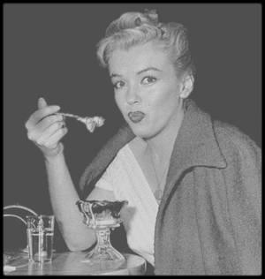 1952 / Marilyn dégustant une glace sous l'oeil du photographe Andre DE DIENES.