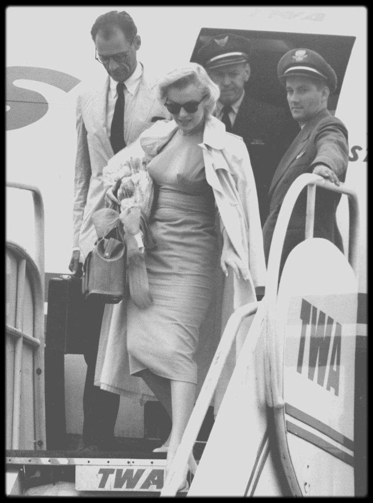 """14 Juillet 1956 / (Part II) Les MILLER partis le 13 Juillet de New York arrivent à l'aéroport d'Idlewild à Londres sous la pluie où Marilyn doit tourner avec Laurence OLIVIER """"The Prince and the showgirl"""" ; le couple voyagera avec pas moins de 27 valises. Cet événement de la venue de Marilyn à Londres avait fait la Une des journaux, allant jusqu'à éclipser un très important discours du Premier Ministre Anthony EDEN sur la catastrophe économique en Angleterre. Marilyn et Arthur sont assaillis dès leur descente d'avion à """"Idlewild Airport"""" : près de 70 policiers sont présents pour assurer la sécurité car plus de 200 journalistes et photographes sont agglutinés sur le tarmac."""