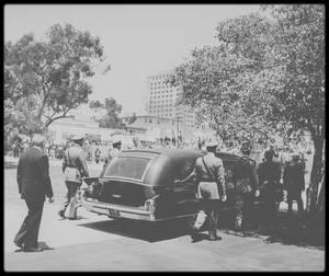 """8 Août 1962 / FUNERAILLES DE MARILYN / Joe DiMAGGIO organisa l'enterrement de Marilyn; il appela Berniece MIRACLE, la demi-s½ur de Marilyn et Inez MELSON, qui s'occupait des affaires de Marilyn.  Berniece MIRACLE autorisa la remise du corps de Marilyn à DiMAGGIO. Il donna l'ordre formel de n'inviter aucun des amis hollywoodiens de Marilyn, car il les rendait responsables de sa mort, moralement sinon concrètement. Quant aux journalistes et photographes, ils furent fermement tenus à distance. Le seul journaliste admis fut Walter WINCHELL, un ami de DiMAGGIO : Les obsèques eurent lieu le 8 août 1962 à 13 h, dans """"Westwood Village Mortuary Chapel"""", située dans le """"Westwood Memorial Park Cemetery"""", à Los Angeles. La police mobilisa plus de cinquante policiers pour contrôler la foule et la circulation : Le service religieux eut lieu dans la plus stricte intimité, et fut célébré par le révérend A.J.SOLDAN, un pasteur luthérien de l'église de """"Westwood Village"""". Il lut le psaume 23, le chapitre 14 de l'évangile de Jean et des extraits des psaumes 46 et 139. On récita le """"Notre Père"""". La cérémonie commença sur les accents de la Sixième Symphonie de TCHAÏKOVSKI et on passa, à la demande de Marilyn, « Over the rainbow » chanté par Judy GARLAND. Carl SANDBURG ayant décliné la demande de Joe DiMAGGIO pour raisons de santé, ce fut Lee STRASBERG qui prononça l'éloge funèbre. Pendant le service, le corps de Marilyn reposait dans un cercueil de bronze ouvert, doublé de satin couleur  champagne. Partiellement exposée, elle portait une robe verte de chez  PUCCI et une écharpe en mousseline verte, qu'elle aimait particulièrement et qu'elle avait portés pour une conférence de presse à Mexico, en février 1962. Allan « Whitey » SNYDER l'avait maquillé pour la dernière fois (il s'était préalablement donné du courage avec une bouteille de gin), fidèle ainsi à la promesse qu'il lui avait faite des années auparavant. A cause des dégâts causés par l'autopsie, Agnès FLANAGAN qui la coiffa ce jo"""