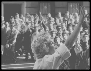"""1954 / Marilyn saluant la foule et les fans sur les marches du bromstowne typique de New York où elle tourne, situé au 164 East, 61 st Street ; """"Sept ans de réflexion"""", sorti durant l'été 1955, est le plus grand succès de l'année pour la """"20th Century Fox"""". Mais la route fut longue et parsemée d'embûches. Le film est l'adaptation d'une pièce à succès qui a tenu le haut de l'affiche à Broadway pendant trois ans. George AXELROD écrit volontiers avec WILDER l'adaptation de sa pièce de théâtre mais les deux scénaristes se heurtent vite au """"Hayes Office"""" qui se charge d'appliquer les règlements du code portant le même nom. On exige d'eux de supprimer toute allusion à l'adultère et d'expurger les dialogues de tous sous-entendus sexuels. Ainsi plusieurs scènes et de nombreuses répliques désopilantes passeront à la trappe, quand d'autres scènes verront leur montage simplement remanié. Dans l'Amérique puritaine des années 50, la plupart des producteurs devaient se plier à ces directives fâcheuses et ridicules. WILDER, très dépité par cette aventure, déclara plus tard : « C'est un film inexistant (…) le film devrait être tourné sans la moindre censure. Ce film fut embarrassant à faire. » On se permettra tout de même d'être moins sévère que le cinéaste, même si on imagine aisément ce qu'un WILDER débridé aurait pu faire d'un tel sujet. C'est bien simple, il nous suffit de penser à un film qu'il réalisera près de dix ans plus tard, """"Embrasse-moi, idiot"""", dans lequel le réalisateur malicieux se lâchera complètement. Mais les dégâts de la censure, comme les agressions répétées des ligues de vertu, n'auront pas minimisé la portée du discours que tient WILDER sur la liberté. Une liberté dont les manifestations s'exercent justement de manière plus violente dans un cadre fermé et régi par des règlements castrateurs. Sous la baguette du cinéaste, on assiste à un plaidoyer énergique et vivifiant pour les fantasmes sexuels, nécessaires au bien-être et à l'équilibre de tout individu."""