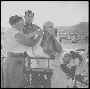 """1960 / RALPH ROBERTS : MASSEUR ET CONFIDENT / Date de naissance : 16 août 1916, à Salisbury, Caroline du Nord. /  Date de décès : 30 avril 1999, à Salisbury, Caroline du Nord. Il avait étudié la physiothérapie et connaissait bien les problèmes musculaires liés aux acteurs. Masseur (et acteur) particulier de Marilyn. Il était étudiant de la Méthode STRASBERG, à """"l'Actors Studio"""", comme Marilyn, et était devenu ami de la famille STRASBERG. Il inspira également le personnage du masseur (et assura la formation dans les coulisses) dans le succès de Broadway « Will success spoil rock hunter ? ». Donald SPOTO affirma, après que Marilyn eut recours à ses services pour le tournage de « Let's make love » (1960), il devint rapidement son ami le plus proche, son confident le plus intime, pour le reste de sa vie. Il joua un petit rôle dans « The misfits » (1961) (un conducteur d'ambulance ) mais il massa aussi les membres fatigués et douloureux des acteurs. Il fut au coeur de la tourmente entre Marilyn et Arthur MILLER dans les derniers mois de leur vie conjugale, et il aida Marilyn à surmonter sa solitude après la rupture. Il la reconduisit chez elle après son horrible expérience au """"Payne Whitney Hospital"""", en 1961. Cette même année il la conduisit, avec sa demi-soeur Berniece MIRACLE, à Roxbury, pour qu'elle y reprenne ses affaires : des livres, des sculptures, de la porcelaine fine, des verres à cocktail et une grande télévision, cadeau de la RCA.  Le 11 juillet 1961 il était à nouveau présent lorsqu'elle quitta le """"Polyclinic Hospital"""" de New York après son  intervention sur la vésicule biliaire. Quand elle retourna à Los Angeles, en août 1961, il partit avec elle. Elle lui loua une chambre au """"Château Marmont Hotel"""", à dix minutes de son appartement de Doheny Drive. Fin octobre 1961, elle lui annonça que le Dr GREENSON, pensait qu'il valait mieux que ROBERTS retourne à New York. Il lui obéit mais ils restèrent en contact. En mars 1962 il revint à Los Angeles pour aider Mar"""