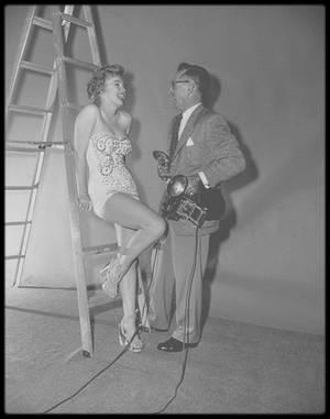 """1952 / Dans les coulisses du tournage et d'une session photos avec Earl THEISEN pour le film """"We're not married"""" / SYNOPSIS / Un ensemble de cinq histoires entremêlées sur cinq couples qui, deux ans et demi après avoir été unis par les liens du mariage, découvrent qu'ils ne sont pas (et n'ont jamais été) mariés.  En effet, le juge de paix qui les a unit, Melvin BUSH (joué par Victor MOORE), a célébré les cérémonies quelques jours avant que sa licence ne soit valide. Marilyn interprète la belle Annabel NORRIS, """"Miss Mississippi"""" en titre, en lice pour l'élection de """"Miss Amérique"""". Son mari, Jeff NORRIS (David WAYNE), n'apprécie pas que la « carrière » de sa femme la distraie de ses obligations de ménagère et de mère de famille. La nouvelle qu'ils ne sont pas mariés fait l'effet d'une bombe et réjouit Jeff - sa femme ne peut désormais plus participer au concours de """"Miss Amérique"""" -, mais il découvre bientôt qu'Annabel a l'intention de participer au concours de """"Miss Mississippi"""", et de la gagner. Le sketch dans lequel figure Marilyn finit sur le remariage du couple. Les quatre autres couples stupéfaits de ne pas être mariés sont interprétés par Ginger ROGERS et Fred ALLEN, Paul DOUGLAS et Eve ARDEN, Eddie BRACKEN et Mitzi GAYNOR, Louis CALHERN et Zsa Zsa GABOR."""