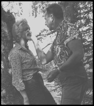 """1953 / En tournage des extérieurs du film """"River of no return"""", Marilyn pose avec des techniciens de l'équipe du film et MITCHUM, ou avec sa doublure lumière Helen THURSTON, répète son texte avec Natasha LYTESS ou encore se fait maquiller par Allan SNYDER. / SYNOPSIS / Marilyn incarne Kay WESTON, chanteuse de saloon dans une ville de fortune, sur la route de la ruée vers l'or, quelque part dans le nord-ouest américain. Elle compte au nombre de ses admirateurs  Mark CALDER (Tommy RETTIG), un petit garçon de 10 ans que son père, Matt (Robert MITCHUM), vient chercher après avoir purgé une peine de prison : il a tué un homme en lui tirant dans le dos (un crime déshonorant- nous saurons plus tard qu'il s'agissait en fait de sauver la vie d'un ami). Matt sauve Kay et son amant, Harry WESTON (Rory CALHOUN), un joueur, leur radeau ayant chaviré près de sa nouvelle maison, une ferme isolée qu'il a acheté pour y vivre avec son fils. En guise de remerciement, WESTON s'enfuit, seul, avec l'unique cheval de Matt en une folle chevauchée, pour rejoindre la ville et faire enregistrer la concession aurifère qu'il a gagnée au jeu. Malheureusement, la ferme est bientôt assiégée par une horde de guerriers indiens, et la rivière est la seule issue. Matt, Kay et Mark doivent affronter les rapides du torrent, les Indiens hostiles et des hors-la-loi. Matt est mécontent d'avoir une femme sur les bras, alors qu'il se bat pour sa propre vie et celle de son fils, d'autant plus que c'est à cause de l'ami de Kay qu'ils sont dans le pétrin.  Cependant celle-ci, malgré sa sympathie envers le jeune garçon, laisse échapper devant lui que Matt a fait de la prison pour avoir tiré dans le dos d'un homme - révélation qui choque profondément le gamin, convaincu désormais de la lâcheté de son père.  Le temps qu'ils rejoignent tous les trois la ville, Kay est tombée amoureuse de Matt. Elle essaie désespérément d'empêcher WESTON, qu'ils ont retrouvé, de se battre avec Matt, alors qu'il n'est même pas armé. """