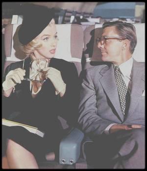 """1953 / Sur le tournage de """"How to marry a millionaire"""" / """"Les hommes préfèrent les blondes"""" connaît un succès public retentissant. La Fox y voit rapidement l'opportunité de prolonger la réussite commerciale du studio en produisant une suite officieuse au film de Howard HAWKS. En novembre 1953 sort donc """"Comment épouser un millionnaire"""" réalisé par Jean NEGULESCO. Le film remplit les salles au-delà de toute espérance et dépasse son illustre aîné au box office. Le pari financier de ZANUCK est gagné haut la main. Le film bénéficie en outre de l'apport tout récent du Cinémascope, nouveau format étrenné la même année par """"La Tunique"""" de Henry KOSTER. """"Comment épouser un millionnaire"""" devient ainsi la première comédie de l'histoire du cinéma tournée en Cinémascope.  La recette apparaît donc fort simple : on prend """"Les hommes préfèrent les blondes"""" et on étend ses attributs dans plusieurs dimensions. Les personnages principaux ne sont plus deux mais trois belles jeunes femmes arrivistes et vénales, la surface de l'écran n'est plus carrée mais rectangulaire, les décors extérieurs sont plus nombreux. On perd en route l'aspect musical de son prédécesseur, mais c'est sans doute pour mieux développer les situations de comédie pure. Et qu'obtient-on en retour ? Certainement une des comédies les plus insipides qui soit. C'est bien malheureux mais cette superproduction tombe souvent à plat, et sa force comique se révèle très inférieure à celle que nous avons l'habitude de rencontrer dans maintes productions américaines du même genre. La satire jouissive du film de Howard HAWKS est absente : les bons sentiments coulent de source et un happy end trop consensuel fait passer à la trappe le semblant de critique sociale dont on espérait naïvement un développement.  En attendant ce qui ne viendra jamais, le spectateur se voit d'entrée proposer une scénographie apte à retranscrire les sensations provoquées par le Cinémascope. Le film s'ouvre sur la prestation d'un orchestre symphonique do"""