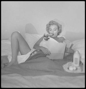 """1953 / Petit déjeuner au lit (verre de lait, carottes et oeufs), dans sa chambre du """"Bel Air Hotel"""", sous l'objectif du photographe Andre DE DIENES."""