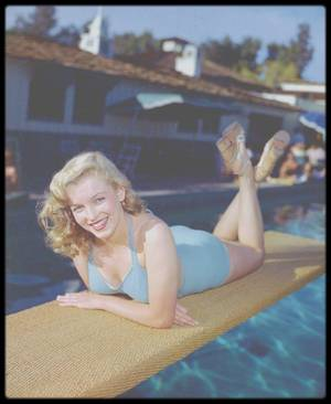 """1949 / """"Racquet Club"""" of Palm Springs, où Marilyn starlette pose pour Bruno BERNARD. / « Les gens étaient captivés quand mon père leur racontait l'histoire de sa découverte de Marilyn MONROE, raconte Susan BERNARD. 1946, c'était l'été indien et la température dépassait les 30°C. Après deux heures sous la lampe de son dentiste, il quitta son cabinet, groggy, et regagna lentement son studio de photo """"Bernard of Hollywood"""" situé quelques rues plus loin. Alors qu'il hésitait à annuler son rendez-vous suivant et à rentrer chez lui, une éblouissante adolescente, aux courbes voluptueuses, passa en roulant des hanches. Elle avait les formes qu'il fallait où il fallait, et se mouvait à la manière d'artistes de strip-tease. Il se demanda si c'était une nymphette qui se prostituait, car en ces temps de guerre le plus vieux métier du monde était une activité prospère. Mais ils se trouvaient dans un quartier trop chic. Alors, il fit quelque chose d'inédit pour lui: il agita la main et siffla la charmante apparition afin qu'elle s'arrête. Une méthode plutôt grossière, admit-il. Puis il lui donna simplement sa carte en disant : """"Mademoiselle, ceci est purement professionnel, j'aimerais faire quelques photos de vous.""""  À six heures le lendemain matin, la vieille guimbarde de Norma Jeane BAKER s'arrêta bruyamment devant ses studios. Elle demanda « Vous pensez vraiment que je peux faire des couvertures de magazine M. BERNARD ? » et il répondit « Mon appareil photo ne ment jamais. » Mon père donna ce premier jet de photos à son ami Ben LYONS, un découvreur de talent de la 20th Century Fox. Cela conduit Norma Jeane à son premier contrat de cinéma. Mon père a été surnommé le """"Roi du Glamour"""", le VARGAS (ndlr : célèbre dessinateur de pin-up pour """"Playboy"""") ou le REMBRANDT de la photographie, mais aucun titre ne lui faisait plus plaisir que """"l'homme qui a découvert Marilyn MONROE."""""""