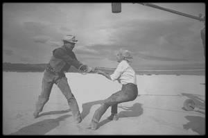 """1960 / Lors du tournage d'une scène (celle de la capture des mustangs) du film """"The misfits"""". / Pendant quatre-vingt-dix jours, des photographes de l'agence """"Magnum"""" se sont relayés sur le tournage de ce film mythique. Une tragédie dont Marilyn est l'héroïne désaxée...  «Encore Marilyn !» s'agaceront les amoureux saturés par l'interminable biographie de ce fantôme qui, depuis 1962, hante l'Amérique. Sur la couverture, pourtant, elle est radieuse. Car il ne s'agit plus ici de l'héroïne du sordide feuilleton politico-policier, mais de la Marilyn mythique : celle du cinéma. En ouverture de l'ouvrage, son nom ne figure pas. La star, c'est le film """"The Misfits"""" (""""Les Désaxés""""). Cette Chronique d'un tournage par les photographes de """"Magnum"""", superbe idée du directeur des """"Cahiers du cinéma"""", Serge TOUBIANA, retrace le film du film avec, en contrepoint, le récit d'Arthur MILLER, scénariste de ce chef-d'oeuvre du 7ème art et à l'époque époux de Marilyn. L'écrivain-dramaturge illustre ses propos avec les clichés de neuf grands photographes de la célèbre agence """"Magnum"""", parmi lesquels CARTIER-BRESSON, Elliot ERWITT, Eve ARNOLD, Cornell CAPA, Erich HARTMAN, Ernst HAAS et Inge MORATH, qui deviendra par la suite Mme MILLER. Commencé dans l'euphorie, servi par un plateau de rêve, le tournage s'avère très vite un cauchemar et placera chacun des participants sous le signe tragique d'une perte. Pour Marilyn, perte de son équilibre. Pour Arthur MILLER, perte de Marilyn. Pour Clark GABLE, perte de sa vie. Pour Montgomery CLIFT, perte de confiance. Pour le metteur en scène, John HUSTON, perte de temps et donc d'argent: le tournage, prévu en cinquante jours, s'achèvera dans la tension et l'épuisement au bout de quatre-vingt-dix. Pour le cinéma, enfin, perte d'un genre, puisque, selon MILLER, """"The Misfits"""" s'inscrit comme le dernier western américain. Situé dans le désert du Nevada, pour mieux signifier par ce décor l'isolement intérieur des personnages. Le sentiment de cette solitude v"""