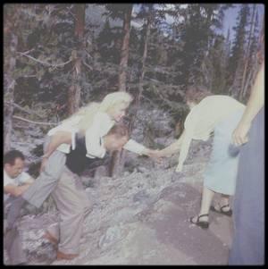 """1953 / Sur le tournage du film """"River of no return"""", Marilyn se blesse à la cheville, dans la fameuse scène du radeau avec MITCHUM et Tommy RETTIG, en glissant sur un rocher ; toute l'équipe est à ses petits soins, jusqu'au réalisateur Otto PREMINGER, Natasha LYTESS, Allan SNYDER ainsi que tous les techniciens du film. Marilyn trouve là un de ses plus beaux rôles bien que les relations avec Otto PREMINGER (agacé par les nombreuses prises nécessaires à sa star) aient été orageuses. C'est le rôle (avec """"Les Désaxés"""" (1961) de John HUSTON) où elle apparaît comme la plus naturelle, le cadre sauvage autant à sa beauté toute sophistication pour une présence charnelle plus libre. Si elle retrouve en partie par instants son emploi de femme enfant inconséquente, Marilyn arbore également un registre plus mature à travers le sentiment protecteur et maternel qu'elle noue avec le petit garçon. """"Rivière sans retour"""" est une ½uvre singulière qui marque la rencontre d'un couple de cinéma mythique avec Marilyn et Robert MITCHUM. Unique western d'Otto PREMINGER, le film constitue pour le réalisateur une commande après laquelle il gagnera son indépendance en créant sa propre société de production. Darryl ZANUCK impose le projet à celui qui est le réalisateur le plus prestigieux de la Fox à l'époque car l'enjeu est de taille. Il s'agit d'asseoir le statut de star fraîchement acquis de Marilyn (""""Niagara"""" d'Henry HATHAWAY, """"Les hommes préfèrent les blondes"""" d'Howard HAWKS et """"Comment épouser un millionnaire"""" ont remporté un fulgurant succès l'année précédente) dans une production à grand spectacle. Le prestige est d'autant plus renforcé avec l'engagement de Robert MITCHUM qui retrouve PREMINGER après l'excellent film noir """"Un si doux visage"""" (1952)."""