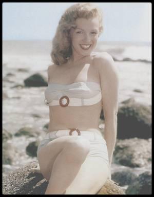 """1947-48 / (Photos de Laszlo WILLINGER, young Marilyn on the beach) / CES ANNEES LA / Lors d'une réception, John CARROLL  présenta Marilyn à Pat DE CICCO, un industriel qui avait lancé avec succès """"Bon-Bons"""", une  friandise vendue principalement dans les salles de cinéma. DE CICCO était un ami de Joseph SCHENCK, l'ancien président de la Fox. Joe SCHENCK, le nabab hollywoodien, organisait de légendaires parties de poker dans son somptueux château, pastiche de la Renaissance espagnole et italienne, situé au 141 South Carolwood Drive, l'un des quartiers les plus chics de Los Angeles :  Des créatures de rêves y étaient également conviées pour remplir les coupes de champagne et vider les cendriers. SCHENCK, Darryl ZANUCK et autres magnats du cinéma jouaient aux cartes. DE CICCO demanda à Marilyn le l'accompagner aux réjouissances. C'est ainsi qu'elle fut présentée à Joe SCHENCK. En 1948, il comptait toujours parmi les personnalités les plus influentes de la Mecque du cinéma. Ancien président de United Artists, ex-patron de la Twentieth Century, puis de la Fox, il exerçait encore une influence considérable sur les grands studios. Habitué à être obéi au doigt et à l'oeil, le vieux baron de la Fox pouvait se montrer magnanime ou irascible, suivant son humeur du moment. Au cours de la soirée ce samedi soir là, Marilyn n'était pas la seule jolie fille présente. Autour de la table de poker s'agglutinait une pléiade de pin-ups, modèles et autres papillons de nuit attirés par les feux éclatants de la rampe. Tout en distribuant  boissons et cigares, la majorité des hôtesses de charme (les « gin-rummy girls »)  semblaient prêtes à rendre des services plus personnels aux joueurs, dans l'espoir de dégoter un petit contrat dans un studio. Ce soir-là, Marilyn resta sagement assise près de DE CICCO, feignant avec grâce d'ignorer les ½illades brûlantes du maître de maison. Dès le lendemain, Joe SCHENCK l'invita à souper en tête à tête et l'envoya chercher dans une rutilante limousine ave"""