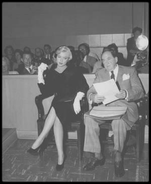 27 Octobre 1954 / (PART II) / DIVORCE AVEC JOE /  Marilyn accompagnée de son avocat Jerry GIESLER, comparut devant le juge Orlando H. RHODES.  Elle dira au juge : « Votre Honneur, mon mari était parfois d'une humeur si noire qu'il restait sans m'adresser la parole pendant cinq jours, même sept jours de suite. Encore plus même quelquefois. Je lui demandais : qu'est-ce qui ne va pas ?  Pas de réponse ; Il m'interdisait de recevoir des visites; en neuf mois je n'ai reçu que trois fois des amis.  La plupart du temps, il ne me témoignait que froideur et indifférence ». Joe se tint à l'écart des débats. Marilyn obtient un divorce provisoire  pour les raisons officielles suivantes :  « Depuis le début de leur mariage, l'accusé a témoigné envers la plaignante d'une grande cruauté mentale, provoquant ainsi de graves souffrances psychiques, et une grande angoisse, tous actes et comportements de la part de l'accusé ne pouvant être imputés à la plaignante, l'accusé est donc coupable d'avoir provoqué la détresse mentale de la plaignante, ses souffrances et son angoisse. ». Moins de deux semaines après cette première audience, Joe pensa que les détectives privés (Philip IRWIN et Braney RUDITSKY) qu'il avait embauchés pour espionner Marilyn avaient découvert des choses intéressantes. Ils avaient suivi Marilyn plusieurs fois à la même adresse, au 8122 Waring Avenue, l'appartement de Sheila STUART, élève et amie d'Hal SCHAEFER. Fou de jalousie, Joe, ses détectives, Frank SINATRA (qui nia plus tard sa présence) et quelques uns de ses copains musclés, entrèrent de force dans l'appartement pour surprendre Marilyn en flagrant délit et donner une leçon à son amant, mais ils forcèrent la mauvaise porte. Cette histoire est restée dans les mémoires comme le « raid sur la mauvaise porte », et une plainte fut déposée par la propriétaire de l'appartement. Mais malgré des mois de tension importante et un divorce, Marilyn et Joe continuaient à se voir.