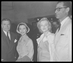14 Juillet 1956 / (PART III) Arthur MILLER obtint un passeport pour accompagner Marilyn en Angleterre, où elle devait tourner son prochain film « The Prince and the showgirl ». Les MILLER décollent de New York le 13 Juillet et le couple arrive à l'aéroport de Londres (Idlewild Airpoprt) le 14 Juillet où une foule immense les attend ainsi qu'une cohorte de journalistes ; Laurence OLIVIER et Vivien LEIGH les accueillent et c'est au sein de l'aéroport qu'une conférence de presse sera improvisée. Une limousine Austin Princess transporta les MILLER dans le Surrey. Milton GREENE et Arthur JACOBS (qui s'occupait des relations publiques de Marilyn) s'y rendirent aussi, escortés par quatre policiers.