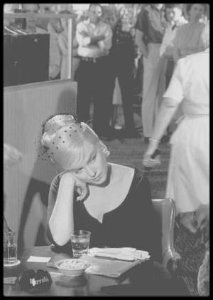 """1960 / Lors du tournage d'une scène du film """"The misfits"""" se déroulant dans un casino de Reno. / Plusieurs critiques soulignent la dimension politique des """"Misfits"""". Pour Madeleine CHAPSAL dans """"L'Express"""", « ce film bouleversant qui nous touche comme une histoire qui nous concerne est aussi une attaque violente de l'Amérique contemporaine ». Ses personnages révèlent en eux-mêmes des contradictions qui sont aussi symboliquement celles de la société américaine. « Ce grand problème de la communication qui hante le monde occidental au début des années 1960 caractérise ces cinq individus qui vivent plus ou moins par procuration pour fuir leurs problèmes », écrit Michel CIEUTAT dans """"Positif"""". Cette revue fait d'ailleurs une analyse très orientée du film, qui selon elle « dresse un constat précis de l'Amérique sous EISENHOWER. Gay, Guido, Perce, les personnages principaux, se veulent des êtres sans attache. Mais l'homo americanus a trahi le rêve des Pères Fondateurs ». Le film « est un douloureux plaidoyer pour la liberté individuelle et une dénonciation d'un monde où toutes les lois morales s'effritent sous l'irrésistible poussée de la machine triomphante « (Les Lettres françaises). Clark GABLE est ainsi pour """"Le Parisien"""" « le symbole d'une virilité qui n'a plus le loisir de s'affirmer dans le monde moderne, et aussi l'expression d'une recherche fondamentale de la liberté individuelle ». Michel CIEUTAT poursuit dans """"Positif"""" : « John F KENNEDY, sur lequel Marilyn fera une fixation, mettra fin à cette fuite en arrière en lançant son programme de la Nouvelle Frontière, autre échappatoire, vers l'avant, dont une grande partie de l'esprit se retrouve dans le film. Tout d'abord dans l'insistance avec laquelle John HUSTON et Arthur MILLER soulignent le thème de la vie à relancer. Le personnage de Roslyn est un catalyseur très """"kennedyen"""" pour ses quatre compagnons. Celui qui s'approche d'elle apprend à repartir sur de nouvelles bases ». Et """"Positif"""" de conclure : « The Misf"""