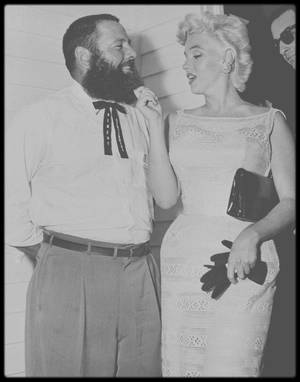 6 Août 1955 / (PART IV) Comment Marilyn, alors la plus grande star hollywoodienne, rapportant des millions de dollars à la Fox, ayant des milliers de lettres de fans par semaine, s'apprêtant à mettre à genoux la Loi des Studios, se retrouva-t-elle dans ce coin pommé de l'Amérique profonde ? (Bement). Retour sur un voyage rocambolesque. Depuis la fin de l'année 1954, Marilyn a quitté Los Angeles pour s'installer à New York, gage de reconnaissance professionnelle pour l'actrice qu'elle désirait devenir. Dans cette nouvelle vie, pleine de rencontres artistiques, elle fait la connaissance de Carleton SMITH, le directeur (et créateur) de la « Fondation Nationale des Arts ». En août 1955, il arrive à convaincre Marilyn de faire un périple dans sa ville natale : Bement, pour « faire entrer l'art dans la vie des habitants de cette petite ville » (dixit Eve ARNOLD). Pour information, Bement du comté de Piatt dans l'Illinois, n'est pas une ville anodine. Elle se retrouve au coeur de l'histoire américaine lorsqu'en 1858, Stephen A. DOUGLAS (sénateur démocrate) et Abraham LINCOLN (avocat fraîchement nommé par le tout nouveau parti Républicain) se mettent d'accord pour une série de débats dans une maison de cette ville de Bement. Ces débats qui eurent lieu dans différents états, ne virent pas la victoire au Sénat de LINCOLN mais ils le firent connaître et mirent en route l'Histoire de ce grand homme. En fait, SMITH avait omis de dire à Marilyn que la ville fêtait en cet été 1955, son centenaire. Les festivités s'étalant sur une semaine se finirent le 6 août. Il est incontestable que SMITH joua de la très grande popularité de la star pour promouvoir cet évènement somme tout mineur, à un niveau national. Comme le dit Eve ARNOLD : « c'était une vraie escroquerie ». Mais la proposition de SMITH était bien alléchante pour la star alors en pleine recherche de reconnaissance artistique. Toute émoustillée par ce challenge de « sensibiliser les masses populaires à l'art », elle téléphona