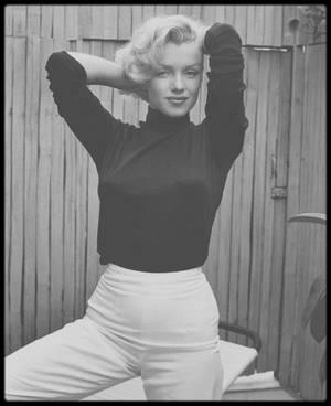 1953 / Marilyn dans le patio de son appartement sur Doheny Drive et prenant sa cadillac (offerte par Jack BENNY, en remerciement pour sa prestation dans l'un de ses shows), sous l'objectif d'Alfred EISENSTAEDT.