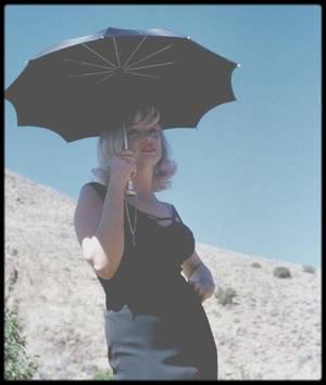 """1960 / Sur le tournage du film """"The misfits"""", notamment avec GABLE et HUSTON. / Marilyn était impatiente de travailler avec Clark GABLE, que son épouse Kay avait accompagné à Reno. GABLE, de son côté, avait pour Marilyn de la sympathie et de la compréhension. Toujours très gentleman, il se plaignait en privé de ses retards mais s'inquiétait pour elle d'une façon toute paternelle. Et le grand professionnel qu'il était ne pouvait admettre qu'elle soit si longue à se présenter sur le plateau. GABLE déclara à Georg CHASIN, son agent, qu'il appréciait Marilyn en tant que cornédienne, mais s'étonna : « Bon sang, quel est le problème de cette fille ? Je l'aime bien, mais je deviens cinglé à l'attendre comme ça ! » / Pourtant, il ne manifesta jamais son impatience sur le plateau. Quand elle arrivait enfin, il lâchait des réflexions du genre : « Pourquoi faut-il que ces jolies filles ne soient jamais à l'heure ? » Il lui arrivait aussi de la pincer, et de dire avec un clin : « Au boulot, beauté ! » Sensible à sa détresse et à sa fatigue, il la faisait toujours asseoir, et ils restaient souvent côte à côte entre les prises de vues pour bavarder des mille et une expériences de GABLE dans le cinéma. Marilyn ne fut pas longue à repérer la faille chez celui dont elle aurait aimé faire son père : GABLE descendait un demi-litre de whisky par jour, et il lui arrivait d'avoir les mains qui tremblaient. Malgré son problème cardiaque et malgré l'interdiction de boire et de fumer que lui avait faite son médecin, il ne renonça pas à ces habitudes de toute une vie pendant le tournage épuisant auquel il était soumis dans le désert du Nevada. On dut refaire un certain nombrede gros plans parce qu'on ne pouvait pas montrer un Clark GABLE tremblant par trente-huit degrés de chaleur."""