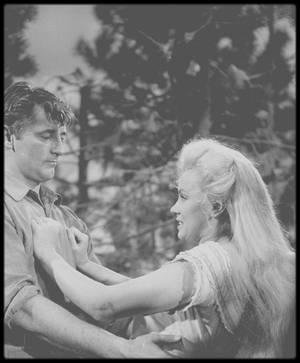 """1953 / Marilyn et MITCHUM dans une des scènes du film """"River of no return"""" / ANECDOTES / A cette période, Marilyn semblait malheureuse et ne voulait pas aller tourner dans un lieu aussi perdu et loin de Hollywood. Le journaliste James BACON l'interviewa à Los Angeles, juste avant son départ pour le Canada : """"Elle semblait ne plus s'être peignée depuis plusieurs jours. Elle s'était barbouillée tout le visage de crème, même ses sourcils, qui étaient tout poisseux. En elle-même, elle restait certainement la Marilyn de toujours, mais au physique, c'était la fille de Dracula ; et je pris congé le plus vite possible."""" Et durant son séjour au Canada, elle continuait de se cacher sous ce masque de crème grasse, même quand elle faisait un saut dans la bourgade voisine. Whitey SNYDER, son maquilleur, finira par lui dire : """"Enlève cette saloperie de ta figure : tu fais fuir les gens !"""" En dehors du tournage, Robert MITCHUM menait joyeuse vie, trinquant, chahutant; il faisait d'ailleurs preuve d'une consommation excessive d'alcool, réclamant aux assistants de lui amener des verres de vodka, ce qui engendrait, là aussi, des conflits avec le réalisateur Otto PREMINGER. Mais c'est MITCHUM qui parvint à faire sortir Marilyn de sa coquille. Un jour, MITCHUM la trouva plongée dans un dictionnaire de psychanalyse, qui ne devait guère satisfaire sa curiosité puisqu'elle lui demanda ce que signifiait """"érostisme anal"""" et ouvrit de grand yeux quand il entreprit de lui expliquer. Une autre fois, toujours selon MITCHUM, la doublure de celui-ci s'approcha d'elle pour lui proposer, en termes choisis, une partouze avec l'un de ses copains.  -""""Tous les deux en même temps ?"""" demanda-t-elle.  -""""Et pourquoi pas ?""""  -""""Vous voulez me tuer !""""  -""""Personne n'est jamais mort de ça que je sache.""""  -""""Oh si. Sauf que ce n'est pas ce qu'on dit officiellement; on appelle ça mort naturelle..."""" MITCHUM rapporta cette anecdote au biographe Anthony SUMMERS en 1982, précisant que Marilyn plaisantait; quant à sa d"""
