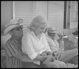 """1960 / Sur le tournage du film """"The misfits"""". / Film crépusculaire par sa thématique, """"Les Désaxés"""" endosse cette dimension de façon plus puissante encore a postériori de par le destin tragique de ses interprètes et son statut symbole de la fin de l'âge d'or hollywoodien. Le film est l'adaptation d'un roman d'Arthur MILLER par lui-même et constitue un cadeau à son épouse Marilyn MONROE, un écrin à son talent avec un personnage largement inspiré de sa vie. C'est aussi une tentative de faire se ressaisir une Marilyn à la dérive depuis quelques années entre addictions aux médicaments, mal de vivre et un mariage qui se délite. Plutôt qu'une thérapie, """"Les Désaxés"""" constituera surtout un testament pour la star qui tourne là son dernier film (terminé puisque le """"Something Got to Give"""" de George CUKOR restera inachevé) tout en trouvant l'un de ses rôles les plus touchants. / Roslyn est une jeune femme se trouvant à Reno pour divorcer. Mélancolique, déçue par les hommes et ne sachant que faire de sa vie, elle va faire la rencontre du cow-boy vieillissant Gay et de son ami Guido. Elle va les suivre pour un temps et découvrir les plaisirs d'un Nevada sauvage oublié, tout en cédant au charme viril de Gay. Ce paradis perdu va pourtant montrer progressivement son envers plus torturé, tandis que de révèlent les fêlures des protagonistes. Marilyn MONROE arrive comme déjà dit sur le tournage dans un état physique et psychologique désastreux qui sur confirmera durant la production difficile entre ses nombreux retards, les absences et les interruptions de tournage - comme lorsqu'en août 1960 elle doit être admise en cure de désintoxication pour deux semaines. Ce rythme épuisera un Clark GABLE vieillissant et en perte de vitesse, qui depuis quelques années accepte enfin son âge dans le choix de ses rôles. Les nombreuses prises dues aux atermoiements d'une Marilyn ne sachant pas et/ou remaniant son texte, le choix courageux de réaliser lui-même ses cascades, tout cela conduira à lui fa"""