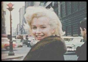 """24 Mars 1955 / Un jour de printemps 1955, un adolescent new-yorkais de 14 ans a passé les plus belles heures de sa vie au côté de Marilyn MONROE. La star a autorisé son jeune admirateur qui la guettait devant un hôtel de Manhattan, à la suivre pendant plusieurs heures de shopping. La caméra 8 mm de son frère au poing, Peter MANGONE a tourné un film amateur couleur de 5'30, l'a visionné une seule fois dans sa chambre du Bronx avant de l'oublier dans une commode. L'an dernier, rangeant la maison de leur père, son frère retrouve le film muet, en parfait état, aujourd'hui transféré en 16 mm. """"J'en avais un vague souvenir, mais quand j'ai vu les images, tout m'est revenu. C'était merveilleux"""", raconte Peter MANGONE, 63 ans aujourd'hui (décédé d'un cancer du poumon le 11 Décembre 2012). Radieuse dans un pull-over noir et manteau brun à col de fourrure, la star sourit, fait des mines, souffle des baisers de la main vers son jeune admirateur, rit à pleines dents sur la 52ème rue. Elle bâille, trébuche ou ôte une poussière de son oeil. """"J'avais lu dans le journal qu'elle venait à New York et qu'elle descendrait à l'hôtel """"Gladstone"""". Alors je faisais l'école buissonnière pour aller la voir, un jour sur deux. Elle me reconnaissait, elle m'aimait bien"""". Touchée par tant de constance, l'actrice lui dit bonjour, signe des autographes et des photos et, un jour qu'elle sort accompagnée de son ami le photographe Milton GREENE, elle l'autorise à la suivre ou à la précéder, sa petite Kodak en main, chez """"Elizabeth ARDEN"""" ou les grands chausseurs de la 5ème avenue. Pas de gardes du corps à l'époque, pour la plus éblouissante star de l'histoire du cinéma américain. """"Elle était si belle, si délicate... Il suffisait de la voir une fois pour que son image s'imprime à jamais en vous! Je n'ai plus jamais été capable de regarder une femme de cette façon"""". C'était l'année où, venant de divorcer de Joe DiMAGGIO et lassée de son image de ravissante idiote, Marilyn avait fuit la Californie et pr"""