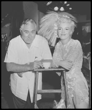 """1954 / Pauses détentes sur le tournage du film """"There's no business like show business"""" ; Dans """"La Joyeuse Parade"""", Marilyn interprète trois chansons : """"After you get what you want"""", """"Heat Wave"""" et """"Lazy"""" (voir tag chanson). Dans le premier acte, sa présence lumineuse et sa voix langoureuse avec ses vibratos donnent enfin un peu de chaleur au film. Et cela même si Walter LANG ne sait absolument pas la filmer, en la desservant avec ses plans larges, alors que Marilyn est bien meilleure chanteuse que danseuse. Nos v½ux sont quand même exaucés avec le tableau """"Heat Wave"""" qui porte bien son nom. La sensualité affriolante de Marilyn y fait merveille. Ses déhanchements lascifs et son jeu de scène suggestif affolent les rétines. Cette séquence, plus gestuelle que dansante, parvient heureusement à la mettre en valeur. Bizarrement, on a enfin le droit à un gros plan, ce qui prouve que même un réalisateur médiocre peut se sentir pousser des ailes devant un tel phénomène. La chanson """"Lazy"""" est également propice à un joli numéro dans lequel Marilyn, accompagnée de Mitzi GAYNOR et Donald O'CONNOR, impose à nouveau sa sensualité et son tempérament. Malheureusement, c'est lors du tournage de ce film que la santé de Marilyn commença à chanceler. Les effets secondaires de sa consommation répétée de somnifères commençaient à se faire sentir. C'est également sur ce plateau qu'elle fit la connaissance de Paula STRASBERG qui allait bientôt jouer un rôle important dans sa vie personnelle et professionnelle. Quant à """"La Joyeuse Parade"""", on laissera le dernier mot à Marilyn : """" un rôle idiot dans un film idiot.. """". Rideau !"""