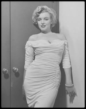 """1952 / Marilyn emprunte une robe au département costumes des studios de la FOX, pour une session photos avec Philippe HALSMAN, qui aura lieu dans son vestiaire, et dont la dernière photo sera retenue pour faire la première COVER de Marilyn du magazine """"LIFE"""" en avril de la même année."""