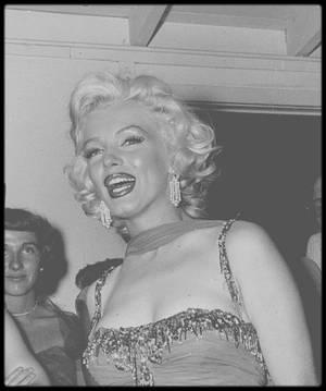 """10 Juillet 1953 / (Part IV) Marilyn participe à une action carricative à """"The Hollywood Bowl"""" (photo), dont les bénéfices seront reversés à l'hôpital """"Saint Jude"""". Pour cette soirée, Marilyn porte une de ses tenues du film """"Les hommes préfèrent les blondes"""". Marilyn est accompagnée de l'acteur Robert MITCHUM (son partenaire dans """"La rivière sans retour"""") ; ensuite elle retrouve l'acteur de sitcom Danny THOMAS sur scène pour co-animer la soirée, et pose pour les photographes dans les coulisses aux côtés du chanteur et acteur Danny KAYE, l'acteur Red BUTTONS, le photographe Bruno BERNARD et le quatuor chanteurs les """"Ames Brothers"""", entre autres..."""