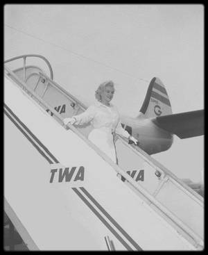 """8 Juillet 1958 / (Part II) MILLER accompagne Marilyn à l'aéroport de New York ; Marilyn s'envole pour Los Angeles afin de préparer le tournage de son prochain film """"Some Like It Hot"""", qui marque son grand retour au cinéma, et Arthur reste à Amagansett pour plancher sur le scénario de """"The Misfits"""" qu'il commence à préparer. Paula STRASBERG, sa coach, et May REIS, sa secrétaire, l'accompagnent. Sur le tarmac de l'aéroport de New York, quelques photographes sont présents, mais surtout des fans, photographes amateurs (tel que James HASPIEL) et des employés de l'aéroport."""