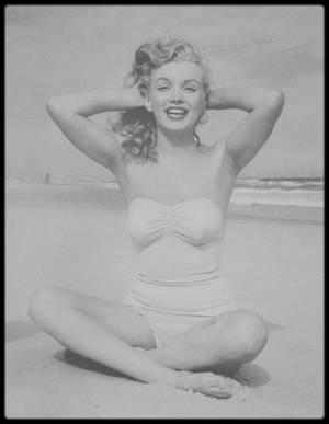 1949 / Marilyn radieuse jouant sur une plage de Tobay beach sous l'objectif du photographe Andre DE DIENES.