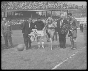 """12 Mai 1957 / (Part VI) Marilyn donne le coup d'envoi d'un match de football opposant les Etats-Unis à Israël à """"Ebbets Field"""" à  Brooklyn (New York). Elle arrive dans le stade en voiture, acclamée par la foule. Elle tape si fort dans la balle qu'elle se foule deux orteils. Cette blessure ne l'empêche pas de rester jusqu'à la fin du match et de remettre le trophée à l'équipe gagnante."""