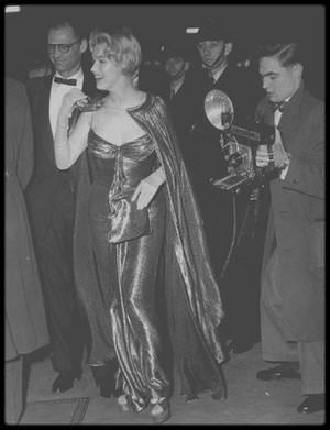 """29 Octobre 1956 / (Part III) Marilyn ainsi que d'autres stars (telles Victor MATURE, Anita EKBERG, Anthony QUAYLE ou encore Brigitte BARDOT) est présentée à la Reine D'Angleterre Elizabeth II, et la Princesse Margaret, lors de son séjour à Londres, alors qu'elle tourne le film """"The Prince and the showgirl"""". Pour l'occasion Marilyn porte une robe lamée or assortie à des chaussures plateforme magnifiques."""